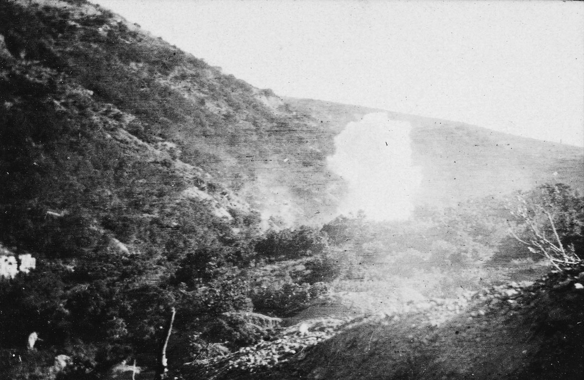 A shell bursting over a valley.