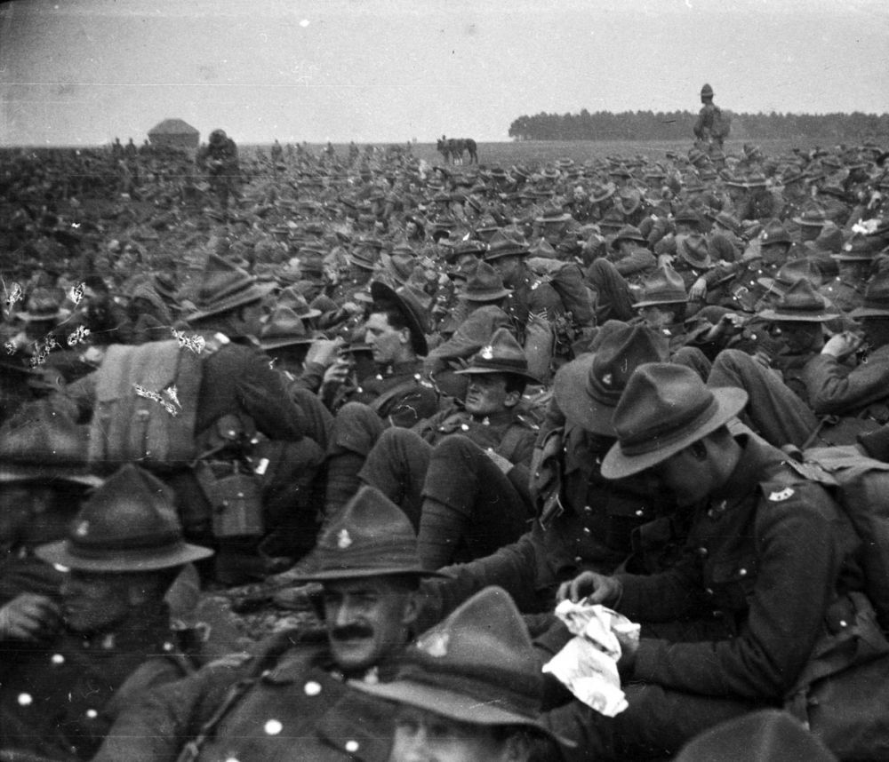 A large group of New Zealand soldiers waiting in a field in full uniform, with webbing, near Sling Camp, England.