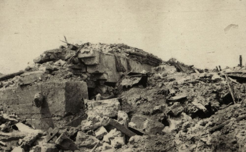 An Allied soldier stands inside a partially destroyed German pillbox, Messines.