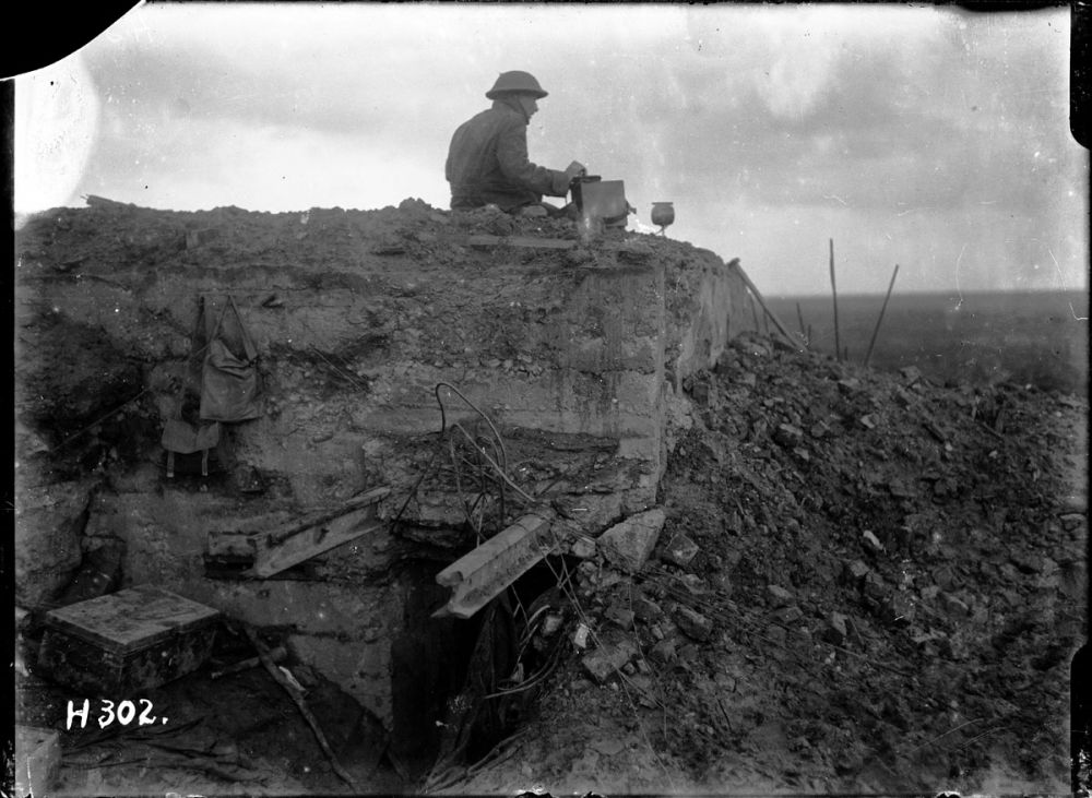A New Zealand signaller operates on a destroyed German bunker at Gallipoli Farm, Belgium, 12 October 1917.