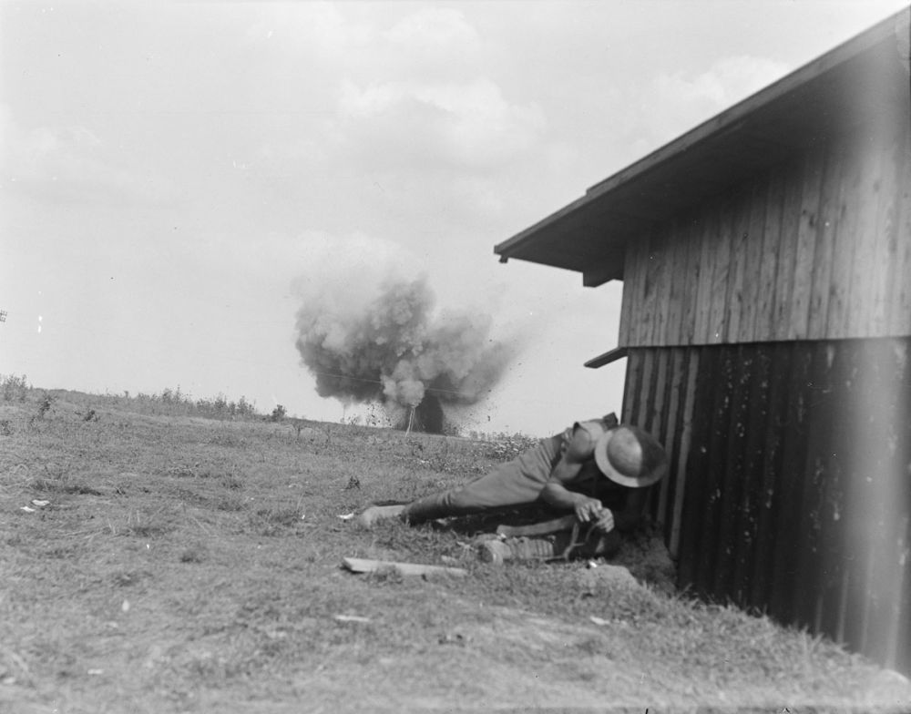 A New Zealand soldier takes cover as a German shell explodes behind him.