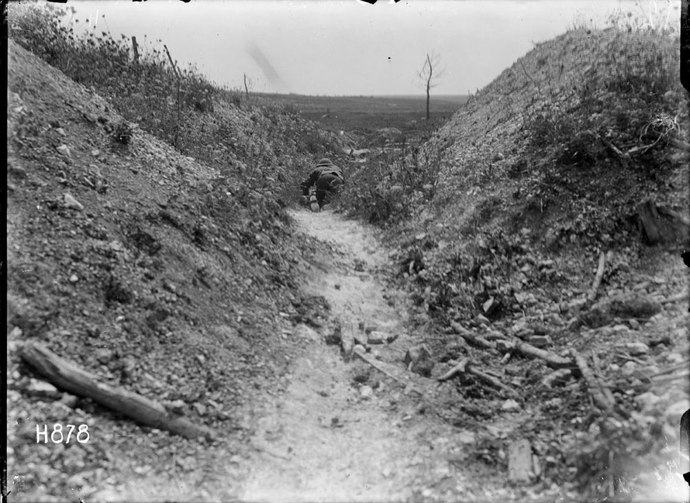 A New Zealand runner crawls through a front line trench trying to avoid enemy machine gun fire. Gommecourt Wood, France, 10 August 1918.