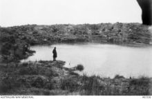 A soldier stands next to a large water-filled mine crater, blown by Australian Engineers at the start of the Battle of Messines, near Wytschaete.