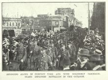 Otago troops marching with Union Jacks flying in the crowd
