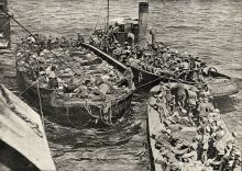Wounded being brought along side an unidentified hospital ship off Gallipoli. A good view of the barges and the lighter towing them. There look to be a number of walking sick and wounded as well as stretcher cases