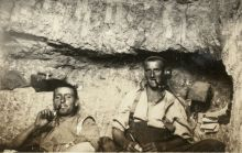 New Zealand troops share a pipe in a dugout at the Signalling Station on No 2 Outpost.