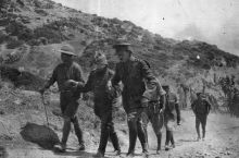 Major Kemal Ohri is led by the hand along the beach by two officers from Anzac headquarters as an envoy to negotiate an armistice to bury the dead.