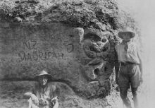 A maori tiki carved into the rock along the main sap to Fisherman's hut. The sign reads : NZ Maori pah and a carved hand pointing to the left indicating the Maori meeting place is to the left. 1915