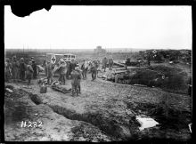 Men at advanced dressing station, prepare a wounded soldier for the ambulance at Somme Farm, Ypres Salient.