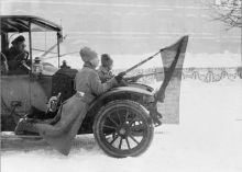 Two Russian soldiers, travelling via motor car through Petrograd, hold red flags affixed to their rifles during the revolution.